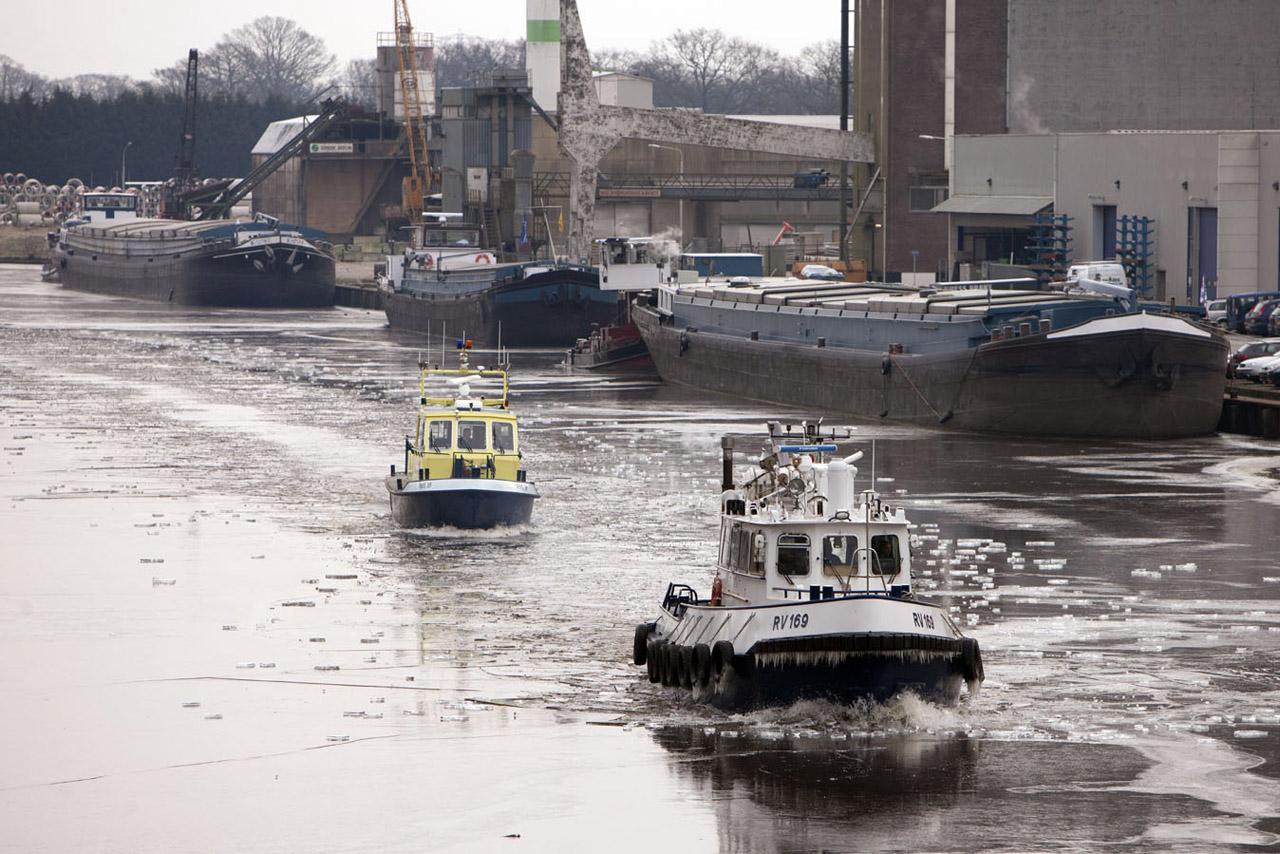 Winter in Nederland, een ijsbreker van Rijkswaterstaat breekt het ijs in het Twentekanaal ter hoogte van Lochem. De vrachtschepen blijven aan de kade liggen vanwege de stremming van de sluis bij Eefde.