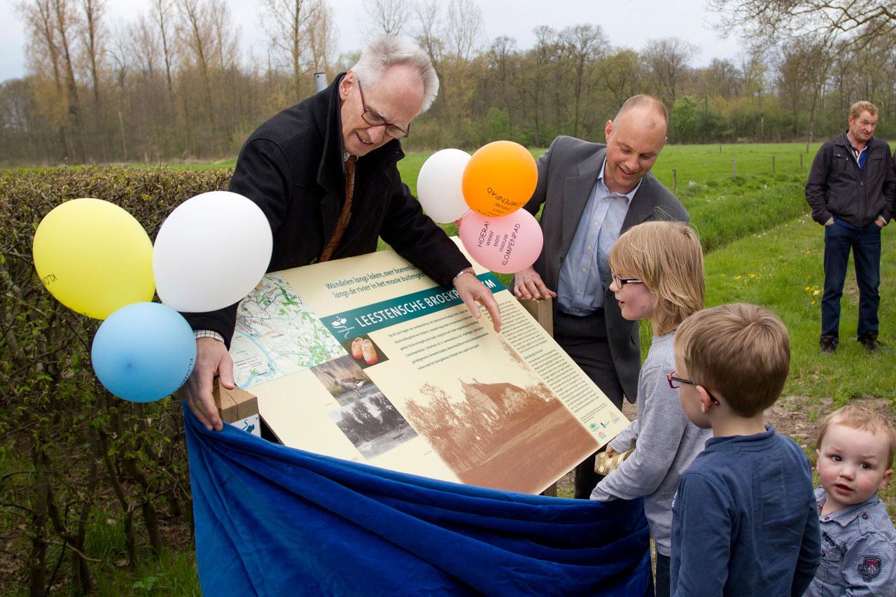 Wethouder Hans La Rose en directeur Arjan Vriend van de Stichting Landschapsbeheer Gelderland staan bij het bord. Twee jongens trekken aan het lint zodat het bord onthuld wordt.