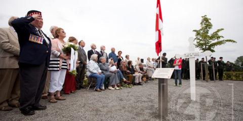 Onthulling van de gedenkzuil bij het witte kruis aan de Looer Enkweg. Frank Periard salueert bij de zuil.