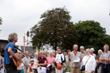 Laatste ludieke poging van actievoerders om bomenkap tegen te gaan in Vorden. Gery Groot Zwaaftink zingt een lied met publiek en bomen op de achtergrond.