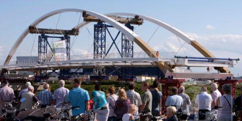 Donderdag stonden honderden mensen op de Loskade in Zutphen om de start van het transport van de nieuwe brug over het Twentekanaal bij Eefde te bekijken. De 117 meter lange brug werd vanaf de kade met grote precisie op een ponton geplaatst waarmee het zaterdagmorgen in alle vroegte over de IJssel naar het Twentekanaal zal worden gevaren.