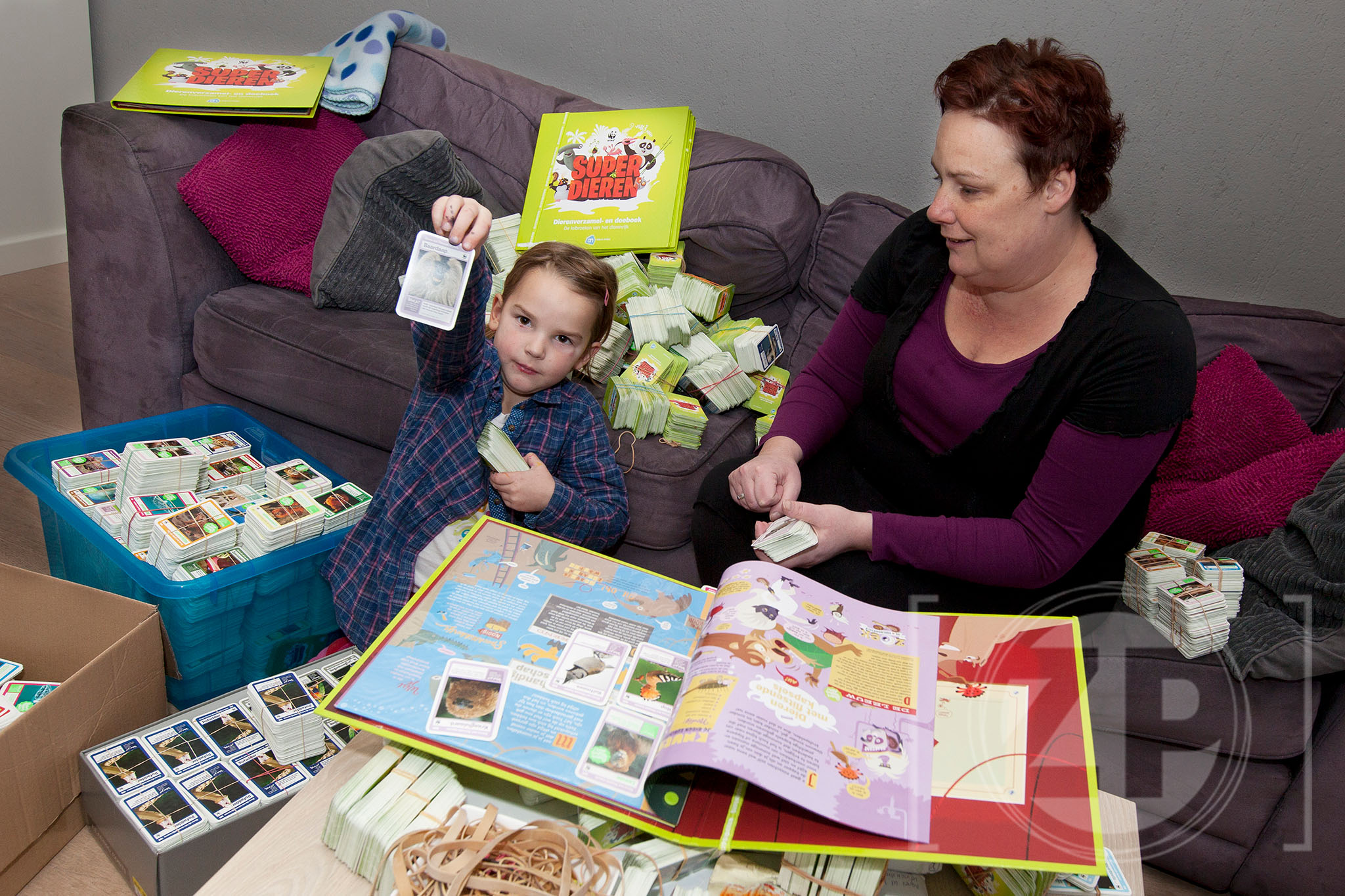 Agnes Klein Haneveld heeft boeken aangeschaft en zamelt dierenplaatjes in om kinderen die het wat minder hebben een mooi cadeau te kunnen geven. Op de foto is ze samen met haar dochter Ise aan het sorteren.