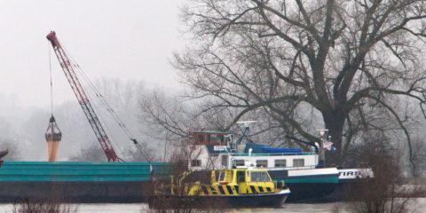 Schip vast in de IJssel tussen Leuvenheim en Bronkhorst. Met een kraanschip wordt de lading van het vastgelopen schip, de Gratias overgeladen naar een ander schip.