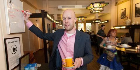 Het Volkshuis doet mee aan uitgestelde koffie. Uitbater Mark Schuitemaker bij het bord waarop de uitgestelde koffie wordt bijgehouden.