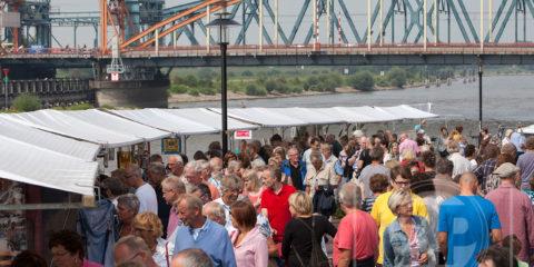 Kunstmarkt langs de IJssel, bezoekers lopen langs de kramen.