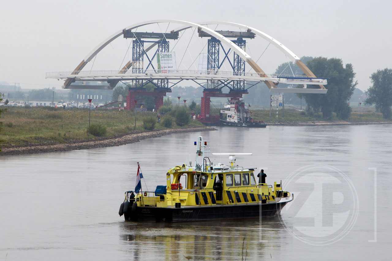 De nieuwe brug, die over het Twentekanaal komt te hangen, is vanmorgen vroeg van de Industriehaven naar de brughoofden in het Twentekanaal gevaren. Om half zes was het al druk op de Zutphense loskade, tientallen mensen waren vroeg op pad gegaan om het transport te bekijken.