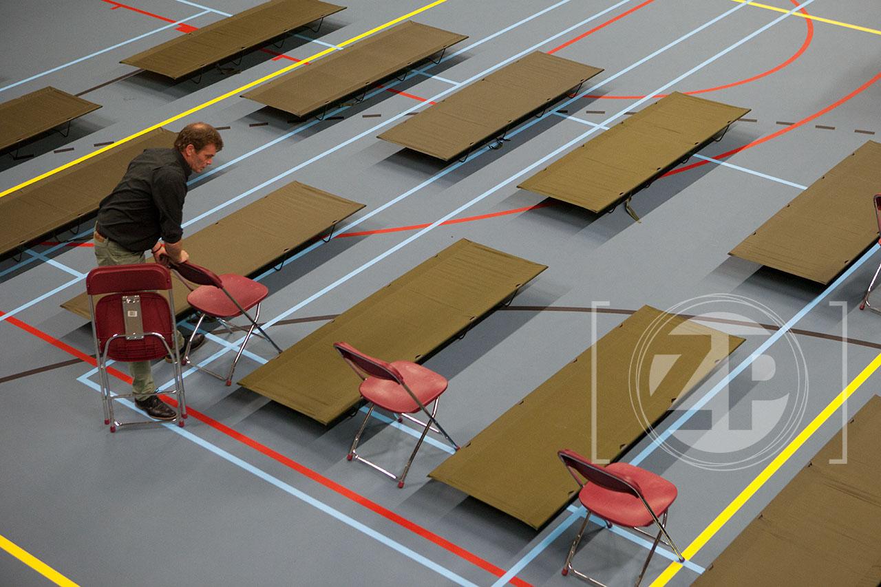 Opbouw van crisisopvang in Hanzehal, veldbedjes in de sporthal. ©Patrick van Gemert