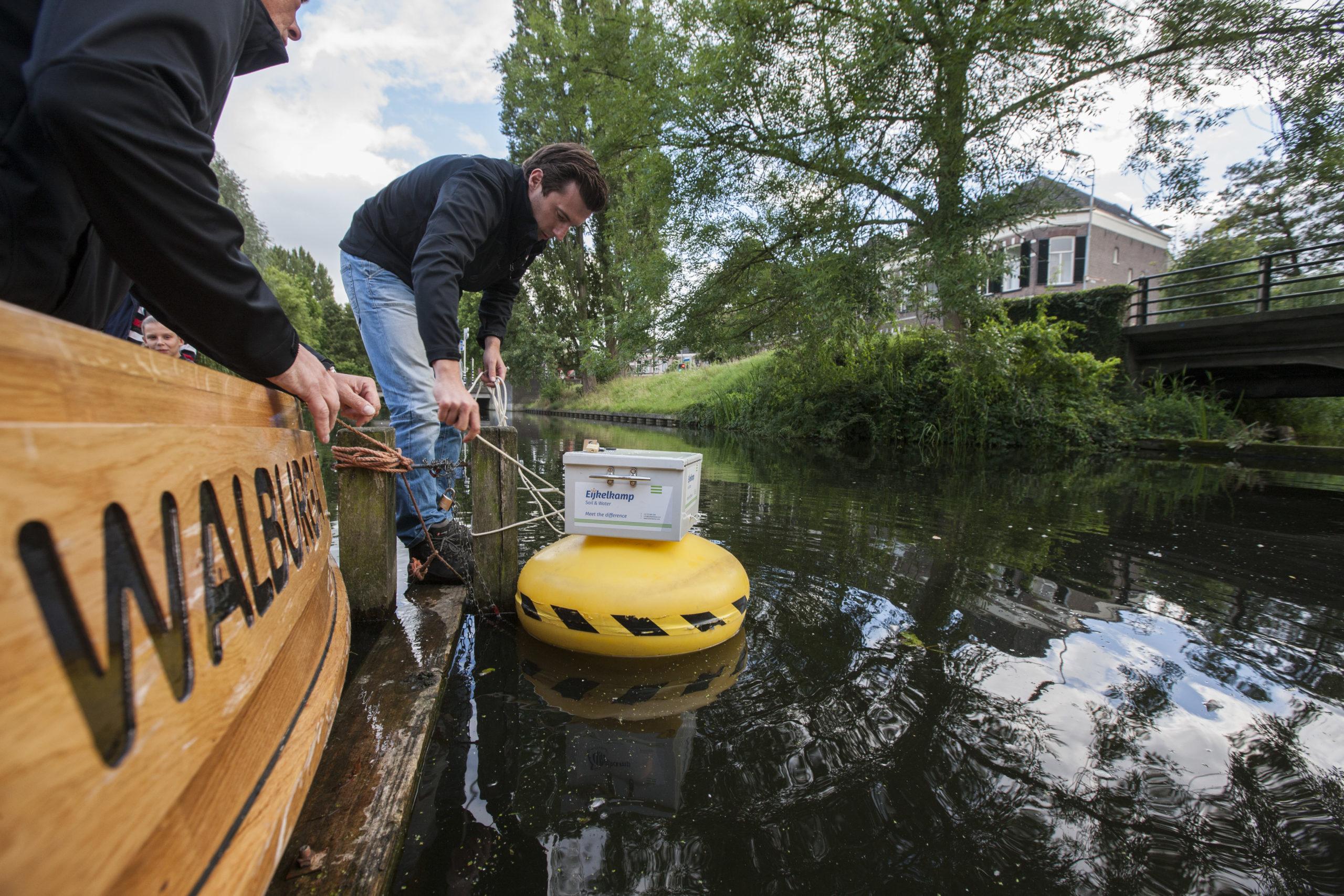 Voor zwemevenement in de Berkel is een speciale boei ontwikkeld met sensoren, die de waterkwaliteit meten. Leon van Hamersveld plaatst de boei in de Berkel. ©Patrick van Gemert
