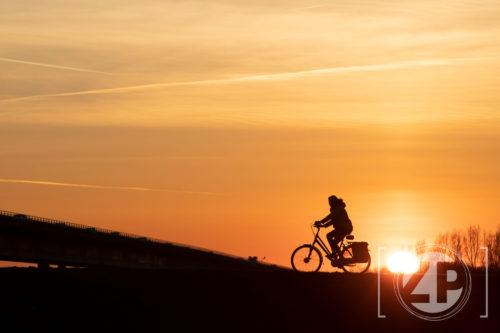 Fietser tijdens de zonsondergang bij de Nieuwe IJsselbrug bij Zutphen.