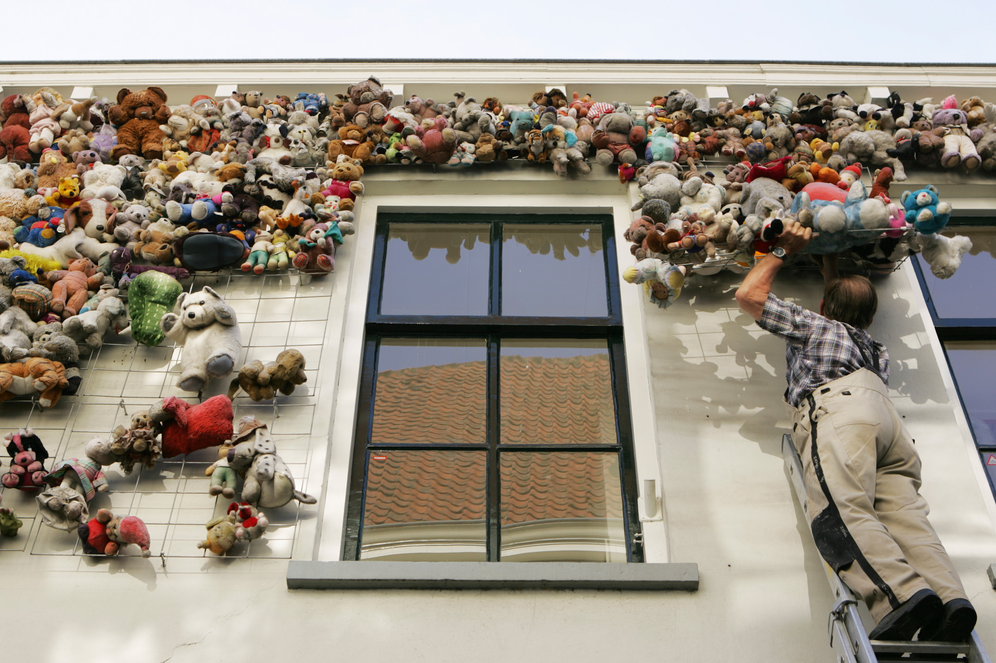 2005 18 juli, Zutphen Een medewerker van bouwbedrijf Peters haalt de knuffels van de muur van de Bornhovestraat 31, de verhuurder Hanzewonen kon geen nieuwe huurder vinden met alle knuffels aan de wand en zo verdween dit zachte kunstwerk uit het Zutphense straatbeeld.