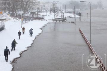 Winter in Zutphen. Mensen lopen door de sneeuw langs de hoog staande IJssel.